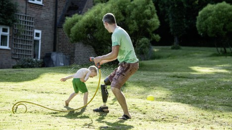 A man wearing a leg prosthesis on his right leg plays in the garden with his son